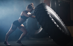 A woman wearing athletic shorts and a sports bra flipping a very large tire