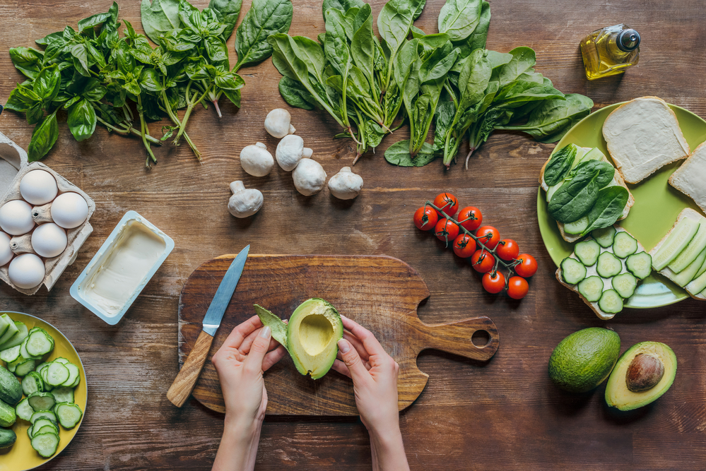 Bird's eye view of two hands holding an avocado on a cutting board surrounded by other vegetables