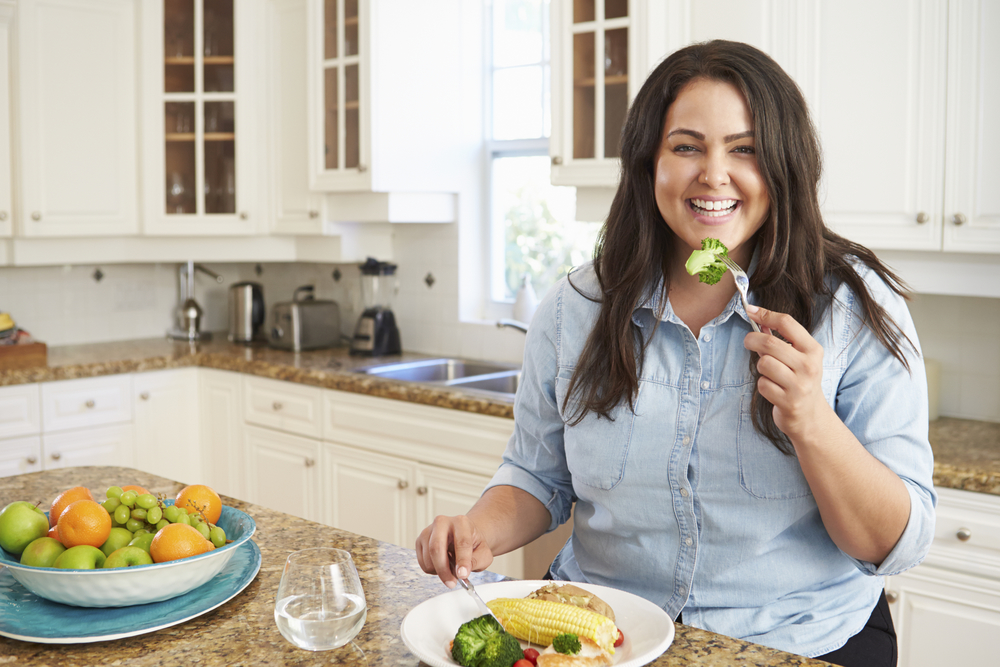 A plus-size woman standing at her counter and eating a meal of superfoods