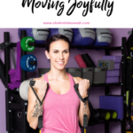 Woman holding exercise handles in a bright purple gym