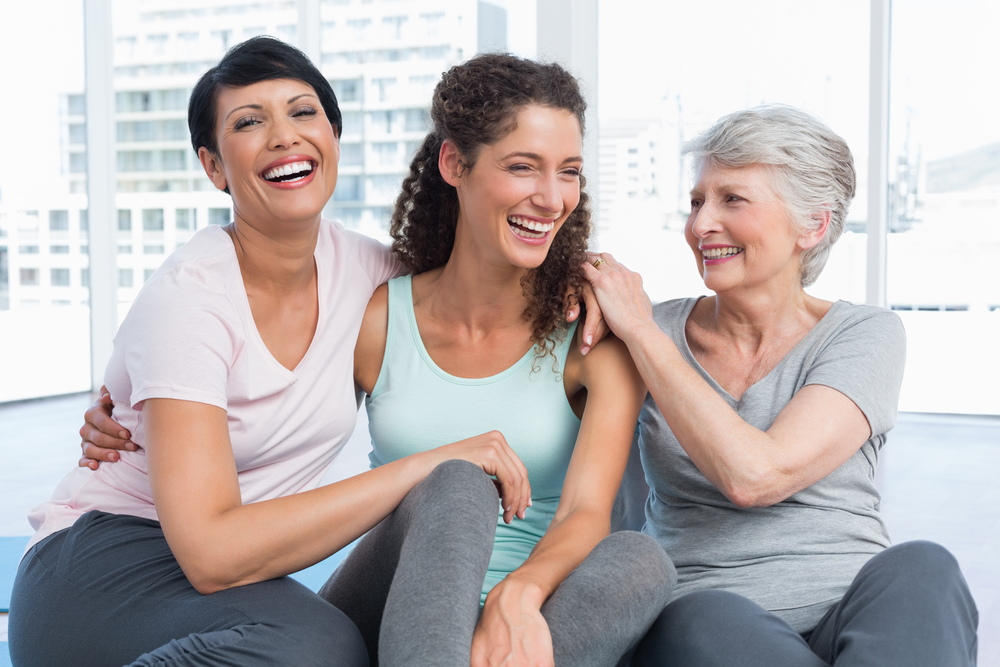 Three femme presenting people of different generations in fitness clothes and sitting on the floor of a fitness studio