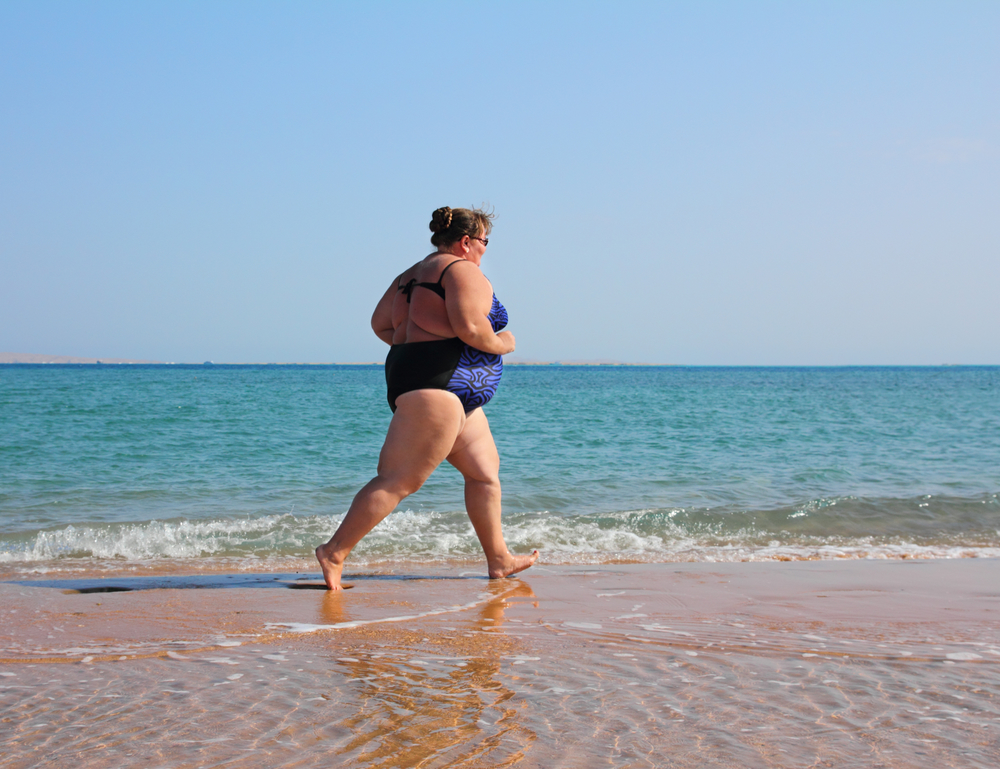 A femme presenting fat person running through the sand on the beach, wearing a one-piece swimsuit