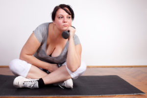 A plus-size, femme-presenting person sits on an exercise mat looking annoyed with a dumbbell resting under their chin