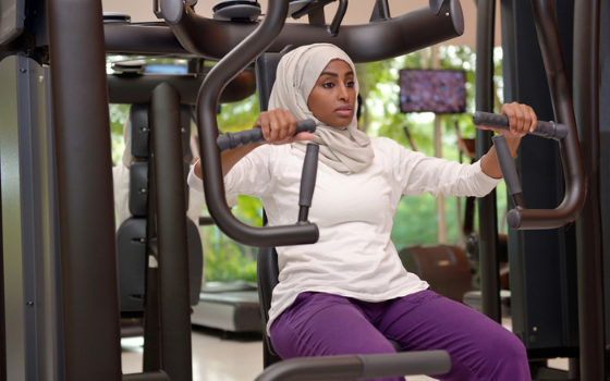 A woman wearing a hijab using a chest press machine at a gym because strength is one of her body positive reasons to exercise