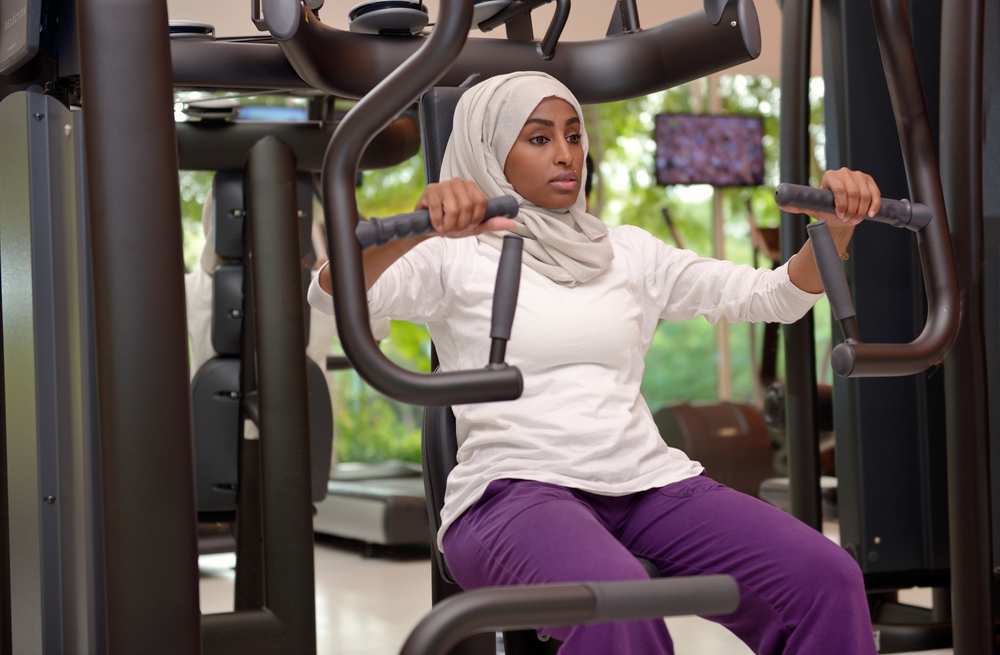 woman in a hijab working out in a gym / reasons to exercise