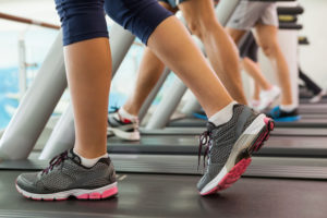 Row of legs of people walking on treadmills at the gym, pondering their body positive reasons to exercise