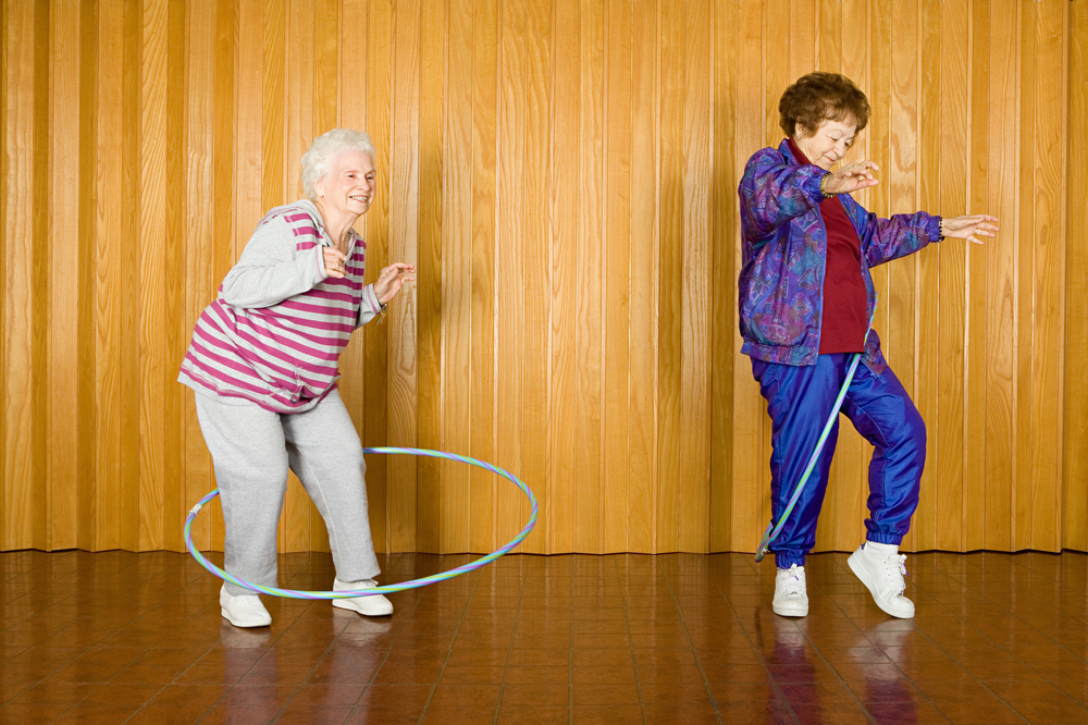 Two senior women wearing sweats and exercising with hula hoops because fun is one of their body positive reasons to exercise