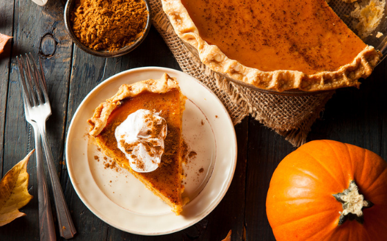A slice of pumpkin pie with a dollop of whipped cream on top sits on a plate. Next to it is the full pie, a mini pumpkin, and some cinnamon in a bowl.