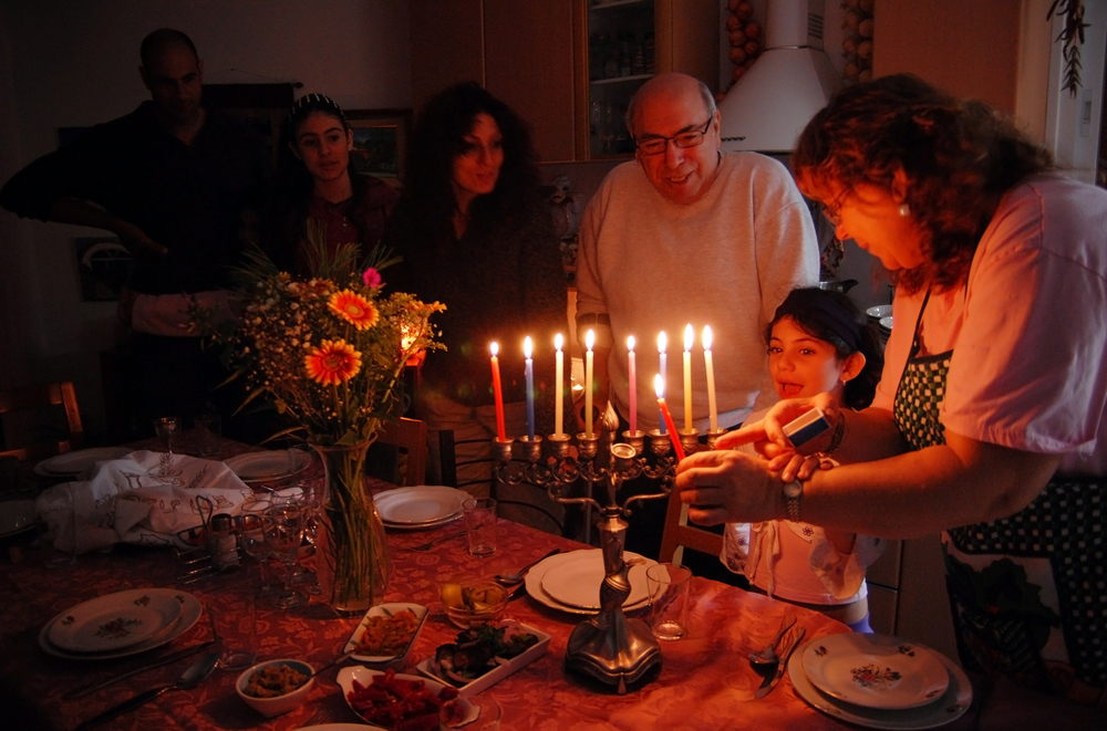 A family gathers around a lit menorah
