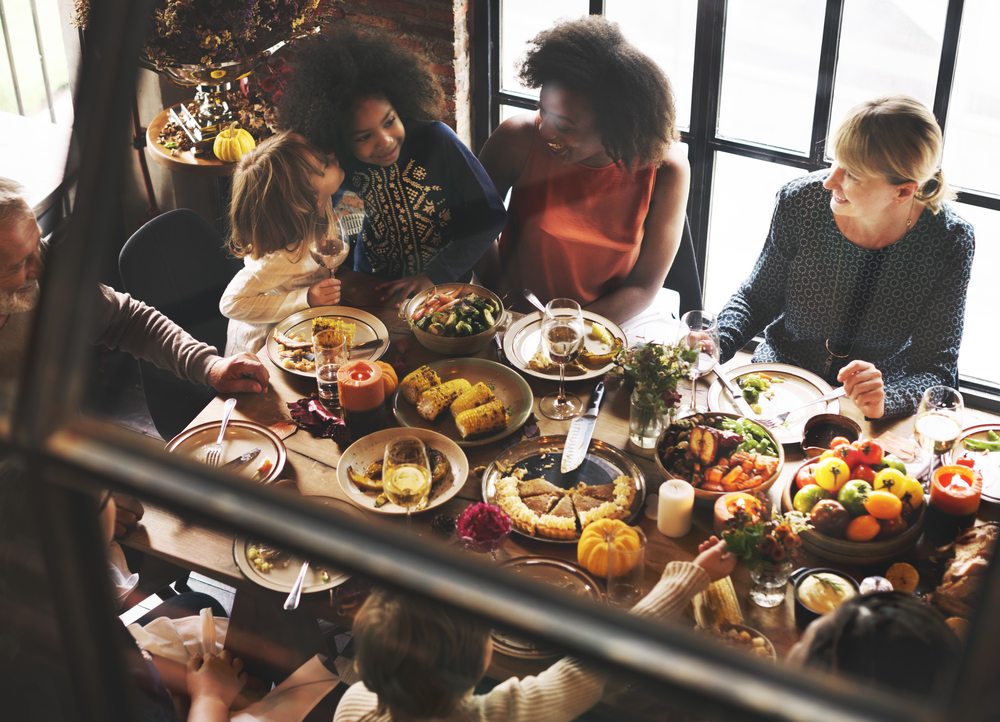 A family gathered around a dining room table overflowing with holiday foods