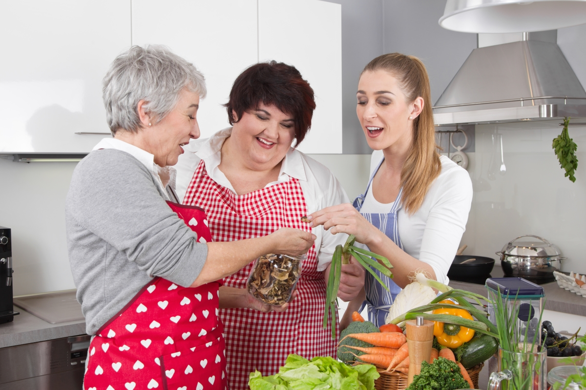 Three femme-presenting people of different generations making a meal together in the kitchen wearing red aprons