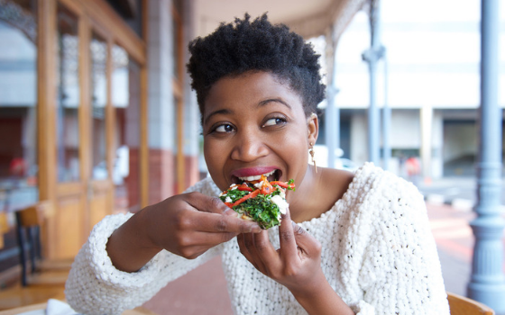 A Black femme-presenting person in a white sweater sits at a table eating a slice of pizza