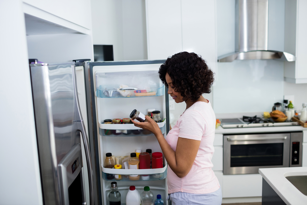 A Black femme-presenting person studies a label on a jar while standing with her fridge door open