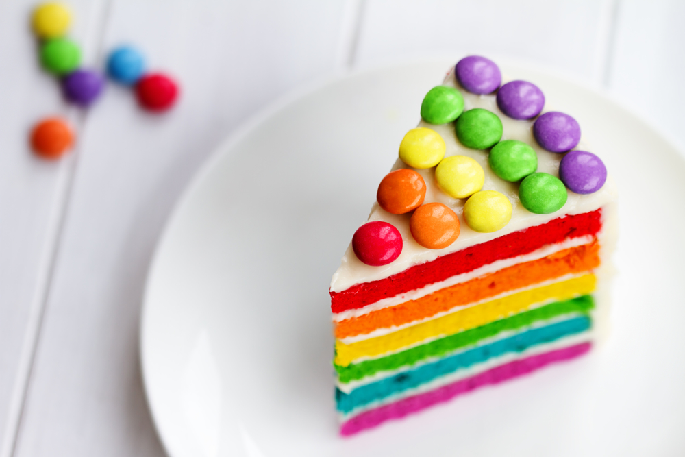 Colorful slice of rainbow layer cake with colorful candies on top