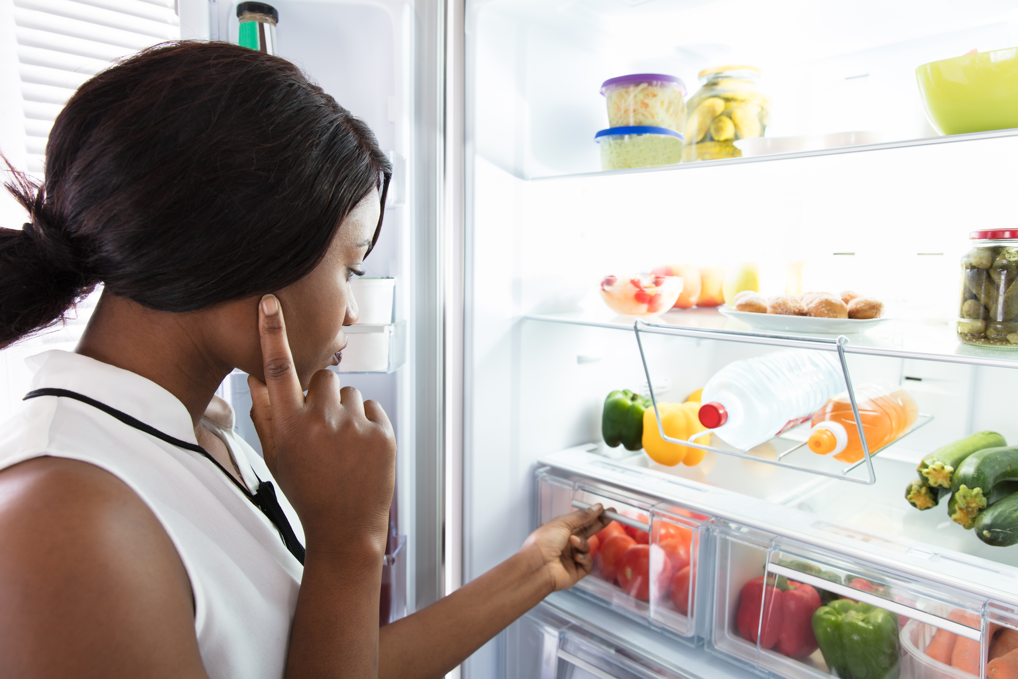 A Black femme-presenting person looking inside the fridge at a variety of vegetables