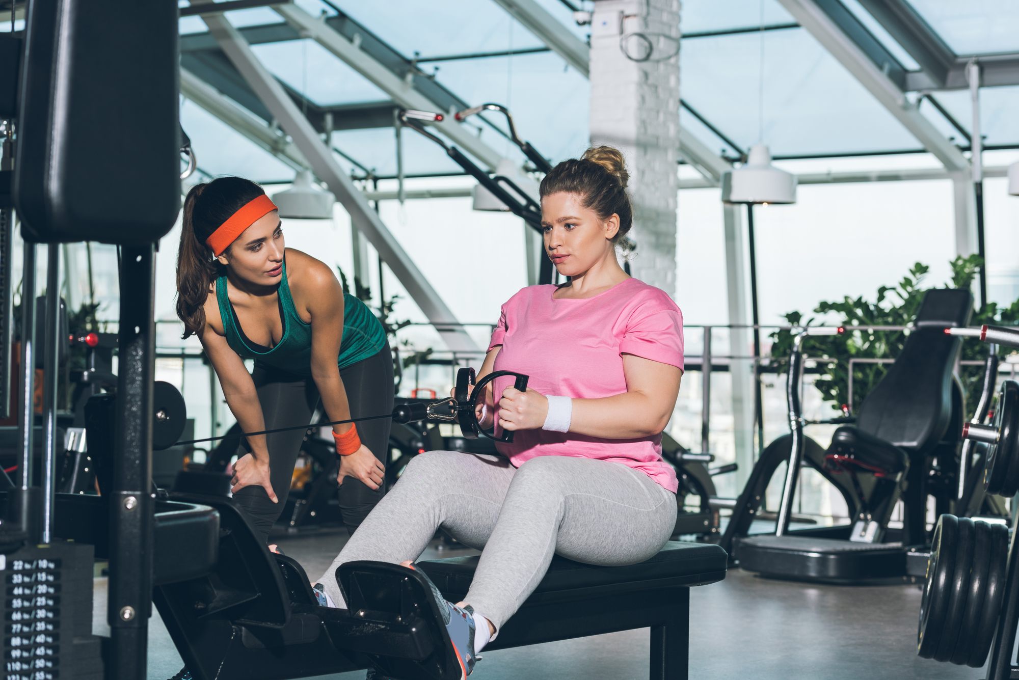 A femme-presenting plus-size woman is seated at a cable row machine with a trainer next to her encouraging her
