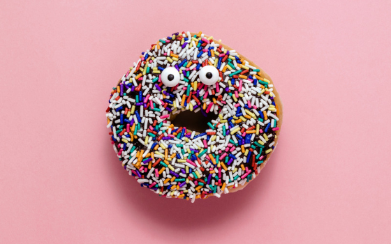A donut with rainbow sprinkles is displayed against a pink background. The donut has googly eyes placed on it that makes it look like it has a surprised expression.