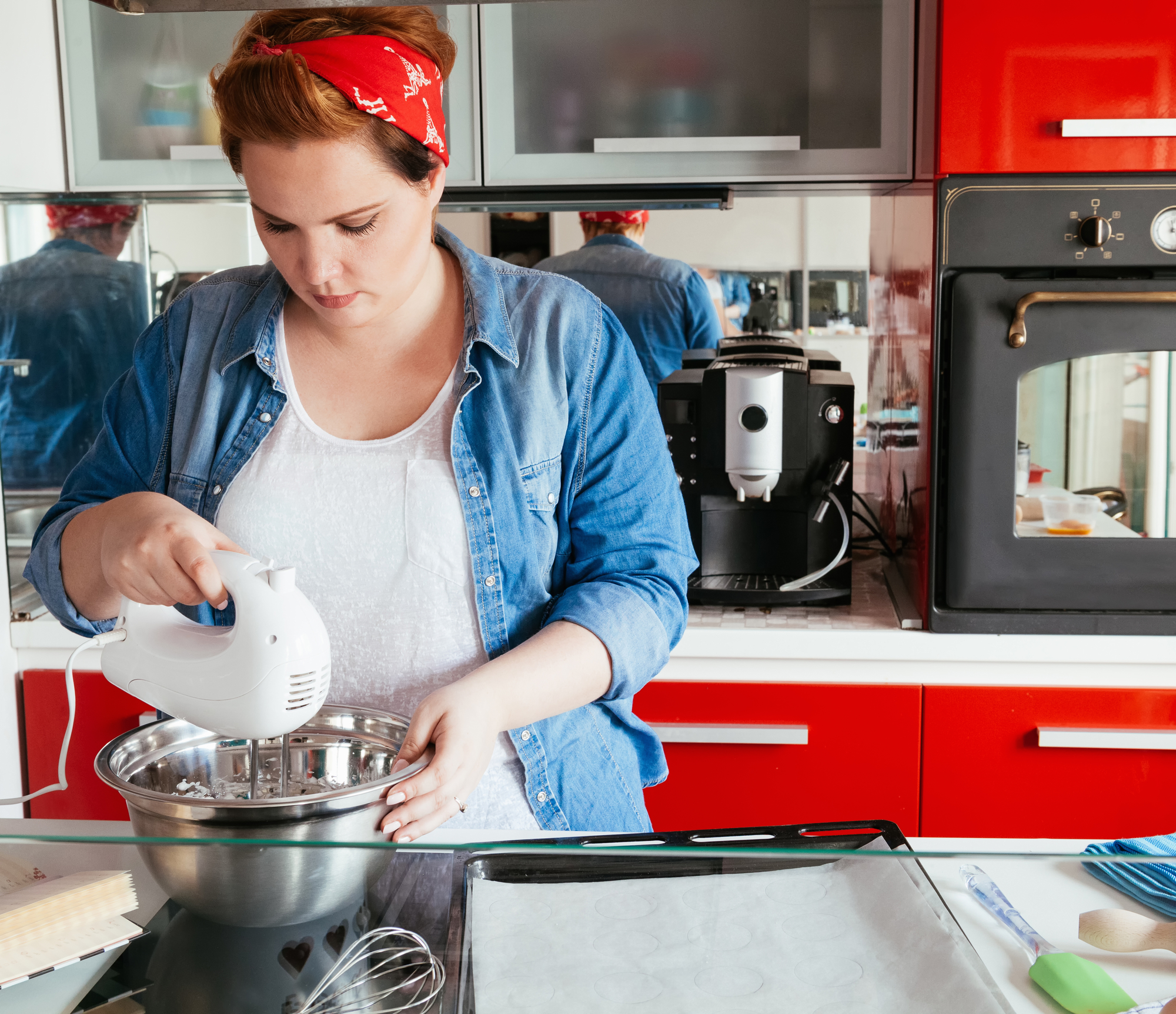 A white woman wearing a red bandana uses a hand mixer to make whipped cream