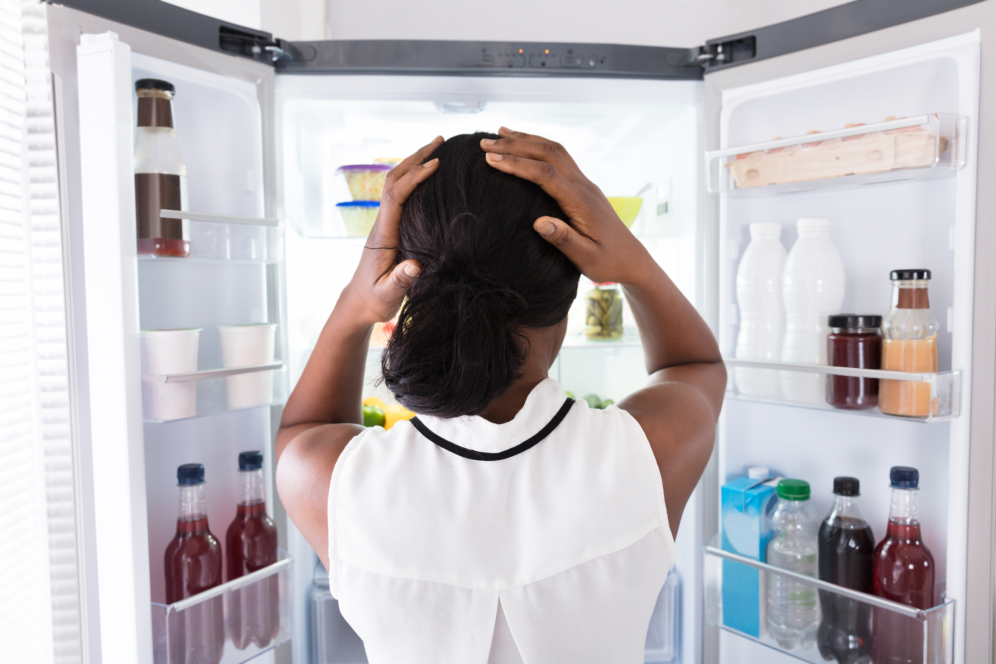 Rear view of a young Black woman looking in the open refrigerator confused about food rules