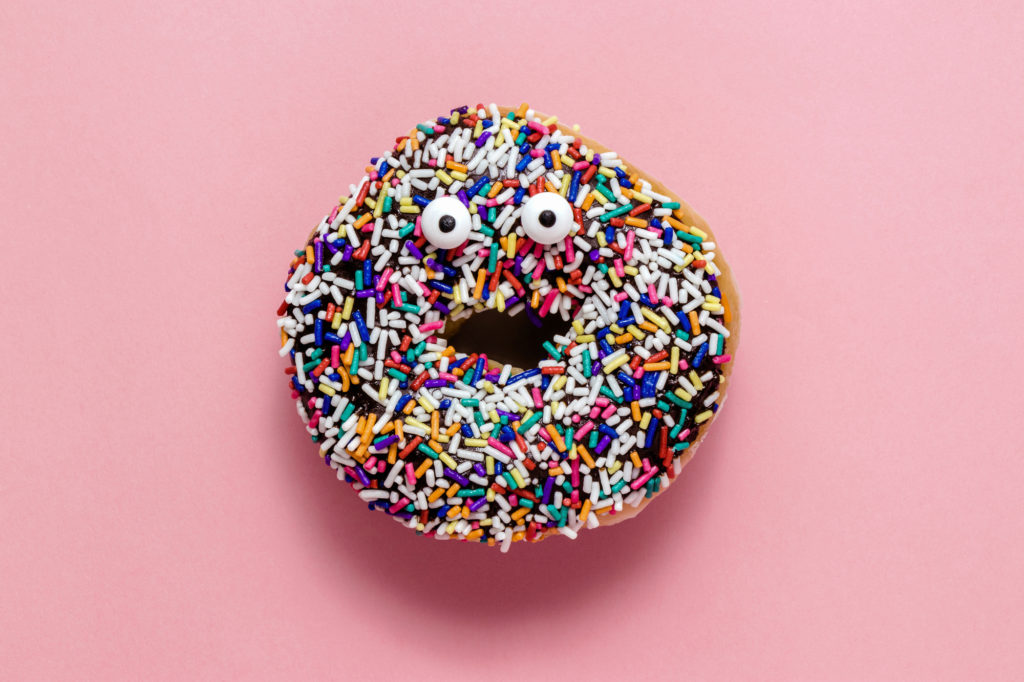 A chocolate donut with sprinkles on a pastel pink background with googly eyes to make it look like it's making a shocked face
