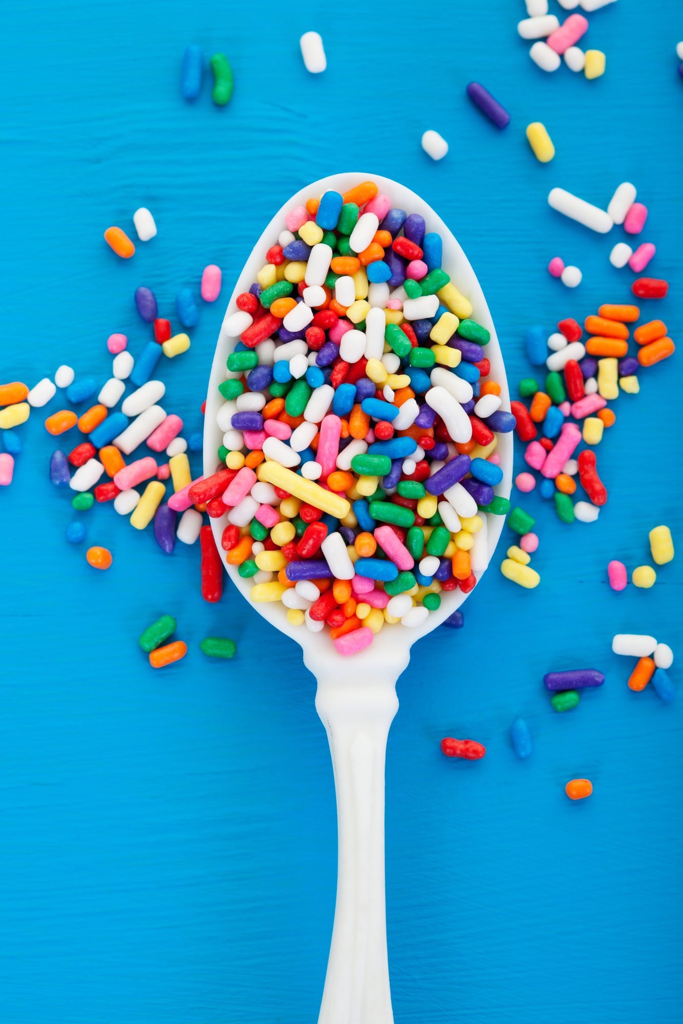 A white spoon with rainbow sprinkles on it and around it against a blue background