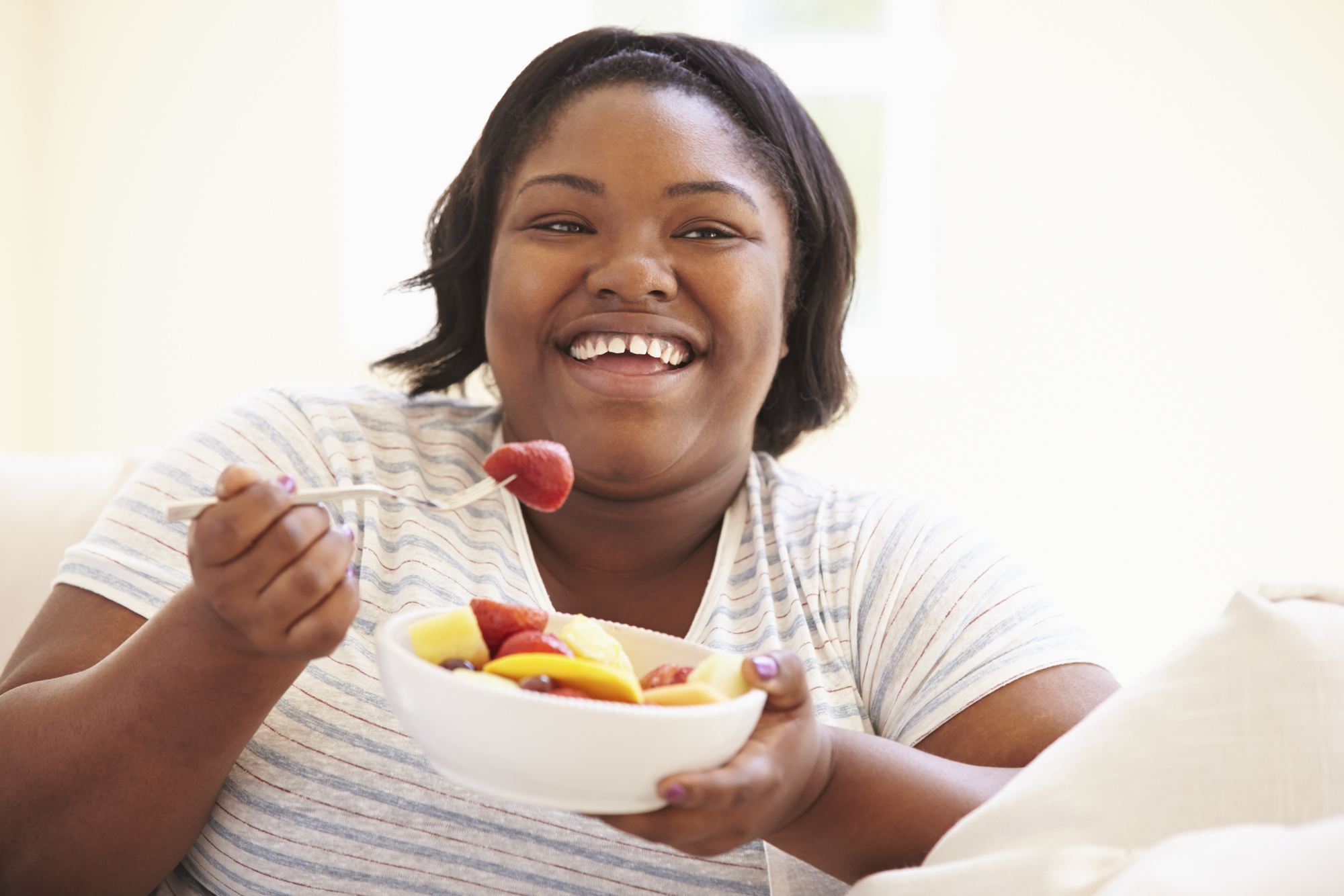 A woman eats a bowl of fruit while sitting on a couch, satisfying her cravings