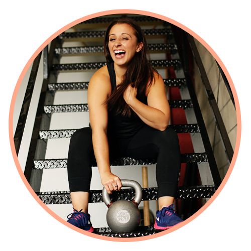 Christina sits on a staircase with a silver kettlebell between her feet. She has one hand wrapped around it and the other is at her chest as she's laughing