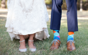 Shohreh holding up the skirt of her wedding dress to show off her sparkly flats and Jason holding up his trousers to show off his colorful socks