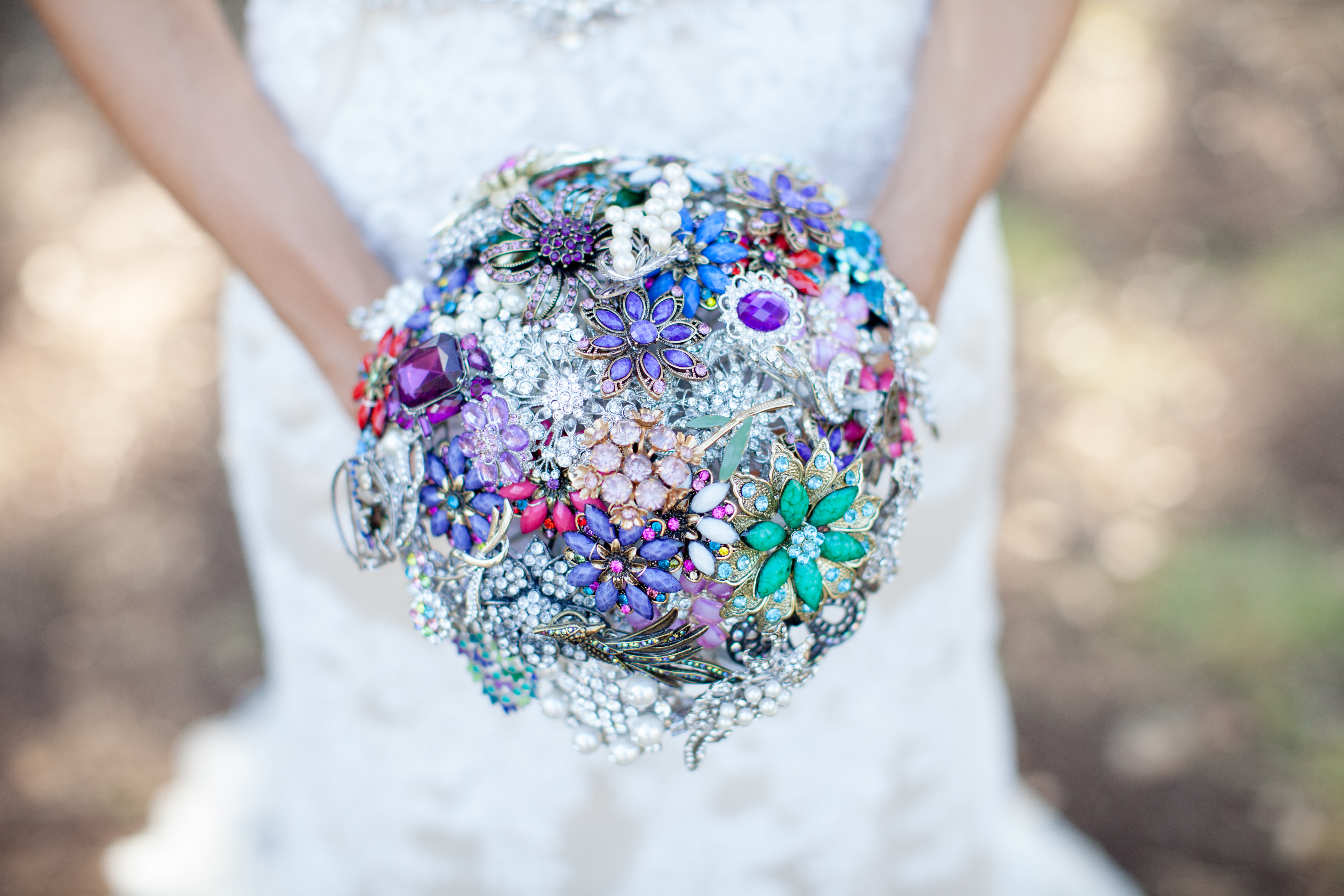 Shohreh's hands holding her colorful brooch bouquet with brooches of different shapes and sizes
