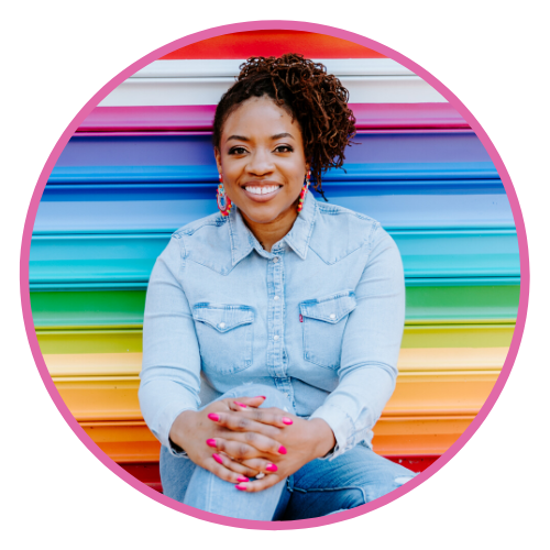 Ayana smiles for the camera in a chambray shirt, sitting against a rainbow colored wall