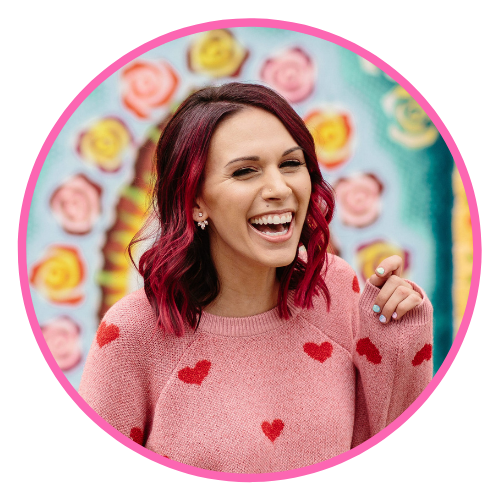 Shohreh is pictured with shoulder-length pink hair wearing a pink sweater with red hearts stitched on it, laughing in front of a colorful painted wall