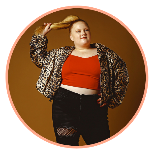 Amanda poses in a red crop top, black ripped jeans, and a leopard print jacket with one hand on her hip and one hand holding her blonde ponytail out to the side