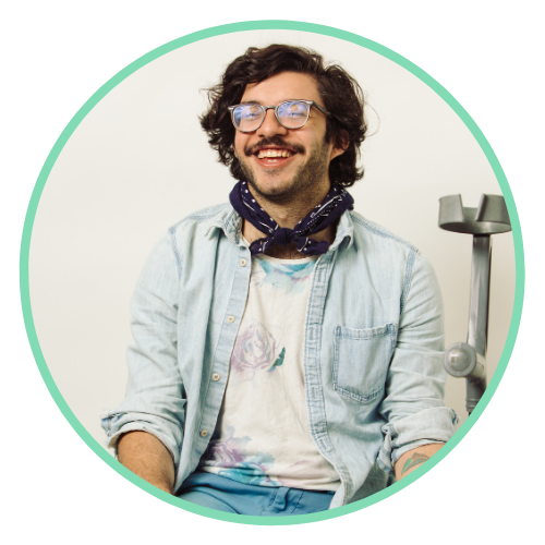 Alex sits, smiling for the camera in a chambray shirt with bandana tied around his neck. His assistive device can be seen right next to him.