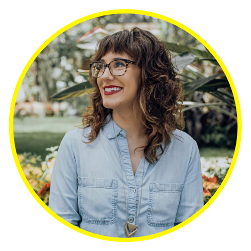 Melissa looks away from the camera to her right, wearing square glasses and a chambray shirt, standing in front of some flowers and foliage outside