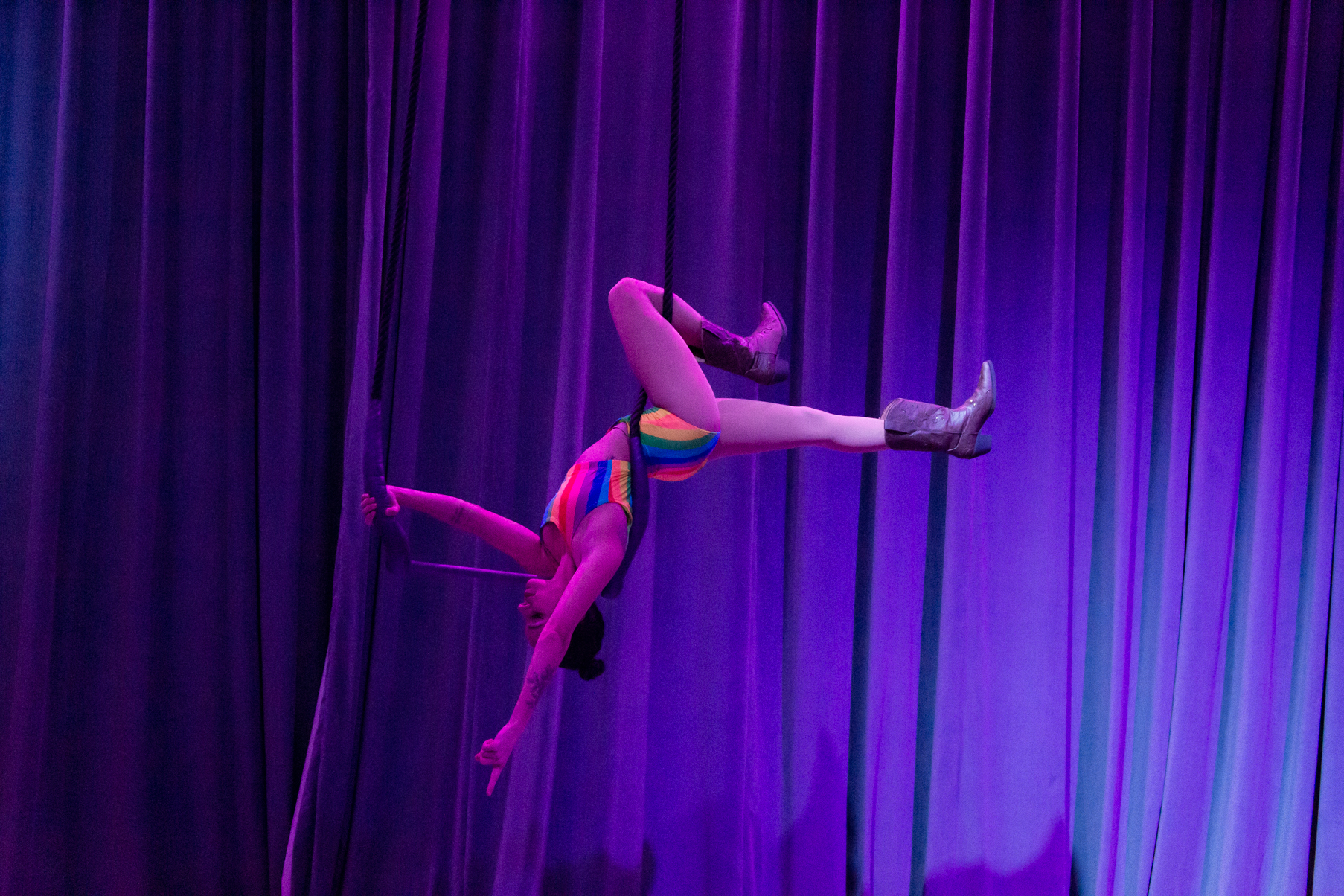 Shohreh holds a pose called bracket on her trapeze, holding her weight in one shoulder upside down on her trapeze bar with her legs extended forward and arms behind her, wearing a rainbow two piece leotard and cowboy boots