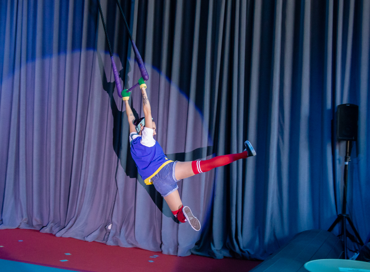 Wearing an Ash Ketchum costume, Shohreh swings on her trapeze doing a flying kick motion with her legs in the air.