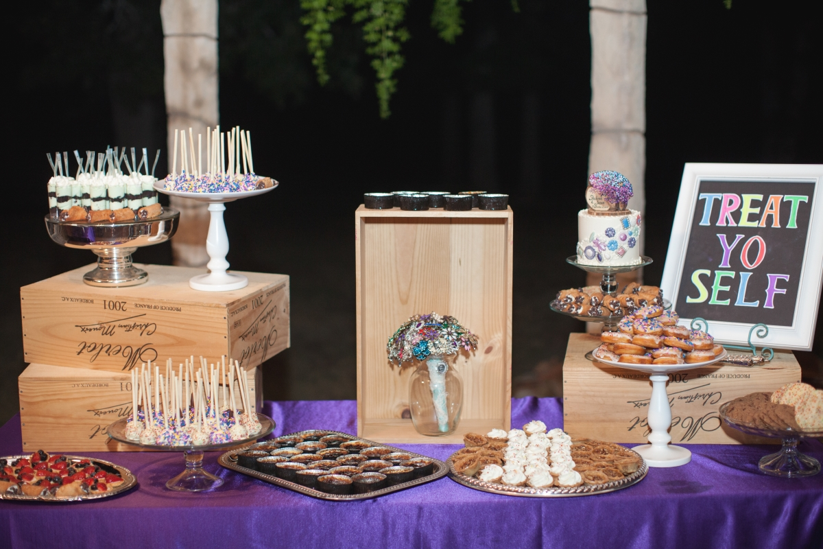 "A spread of different wedding desserts on a table with a purple tablecloth including a sign that says ""Treat Yo Self"""
