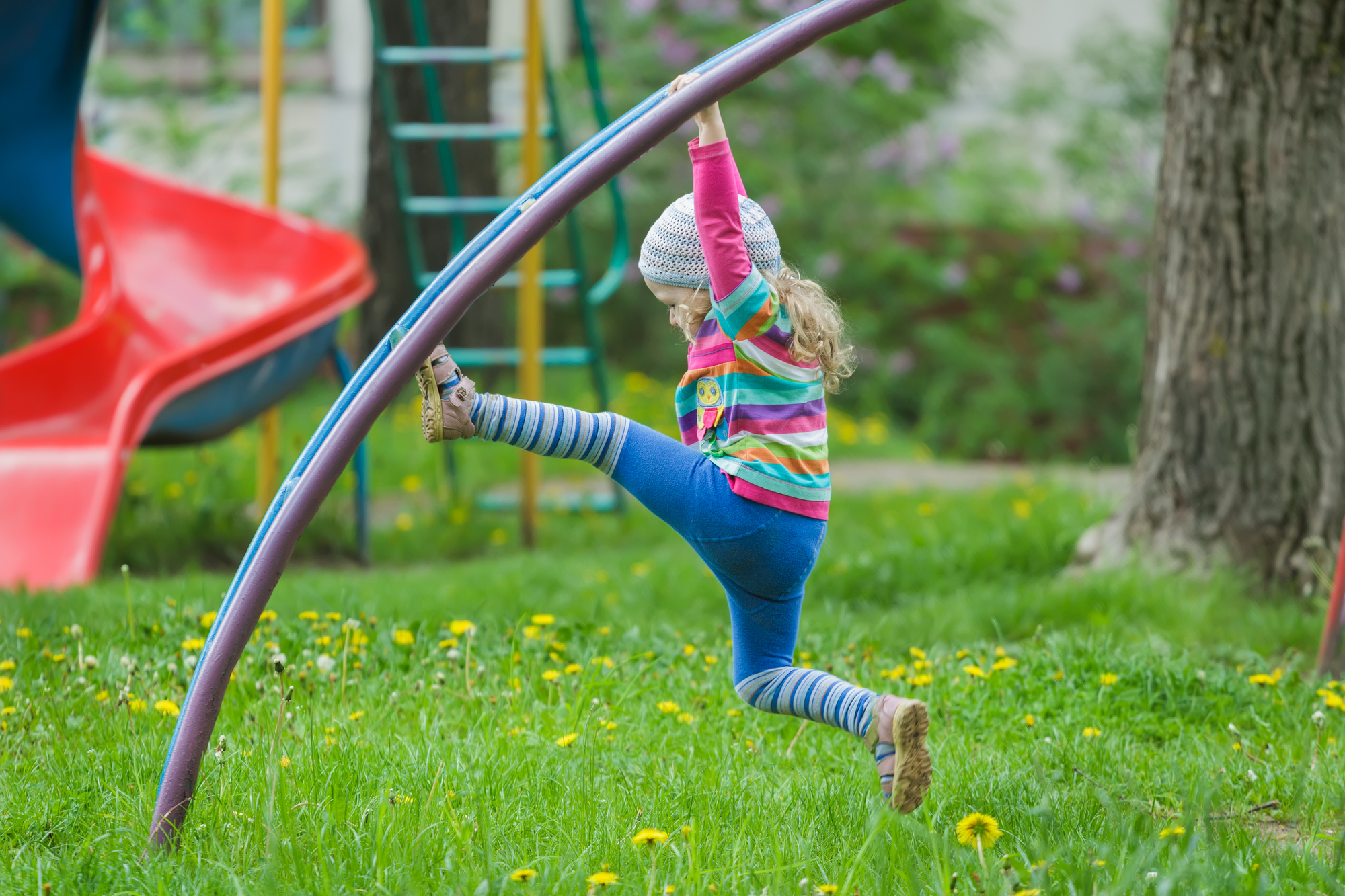 A little girl in a rainbow sweatshirt climbs on a jungle gym on a spring day