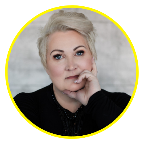 Kelly Diels is wearing black with her short blonde pixie cut coifed. She rests her chin in one hand and stares intently at the camera.
