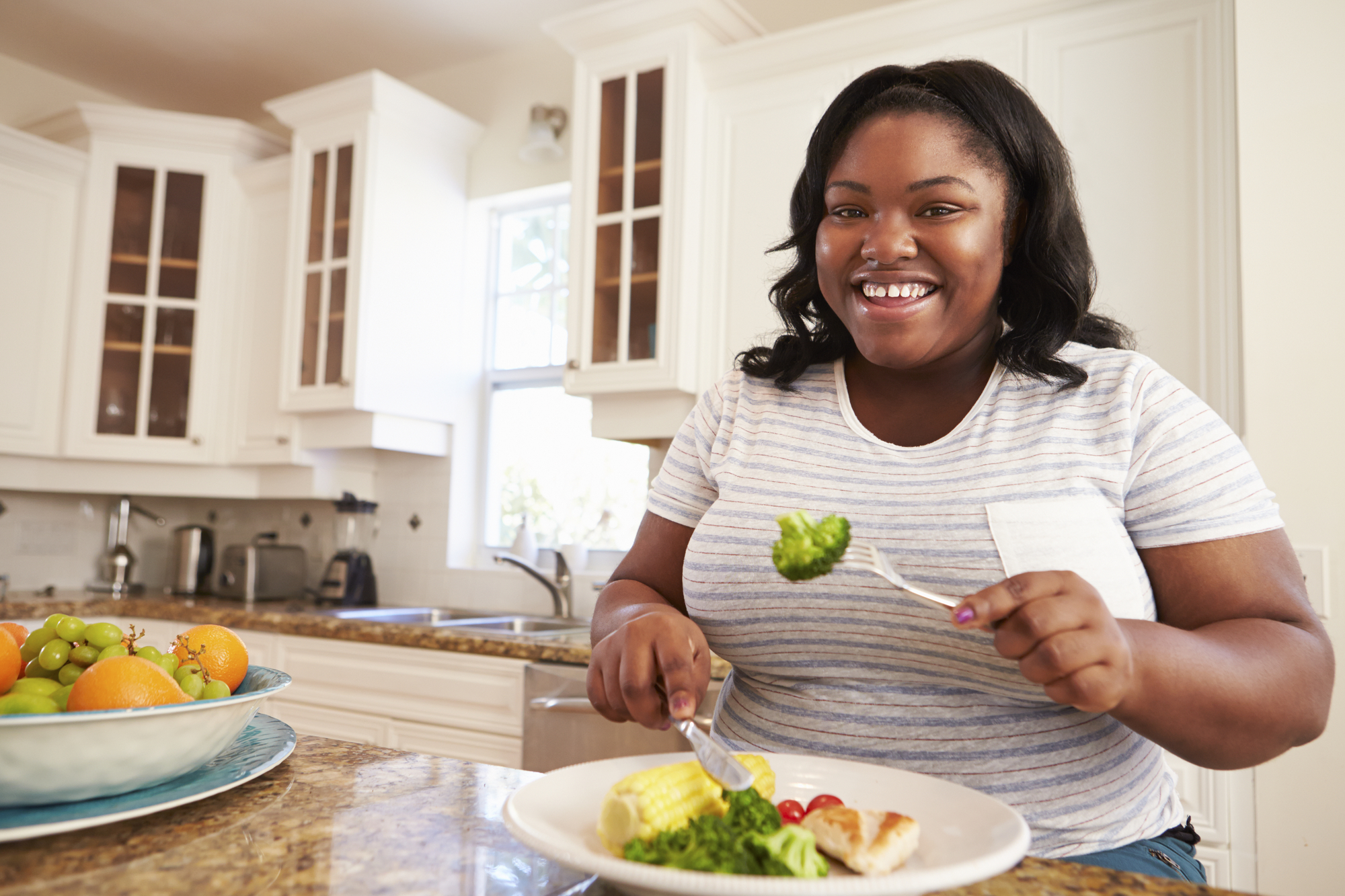 A fat Black woman in a white tshirt sitting at her counter and eating a plate of food with a smile on her face