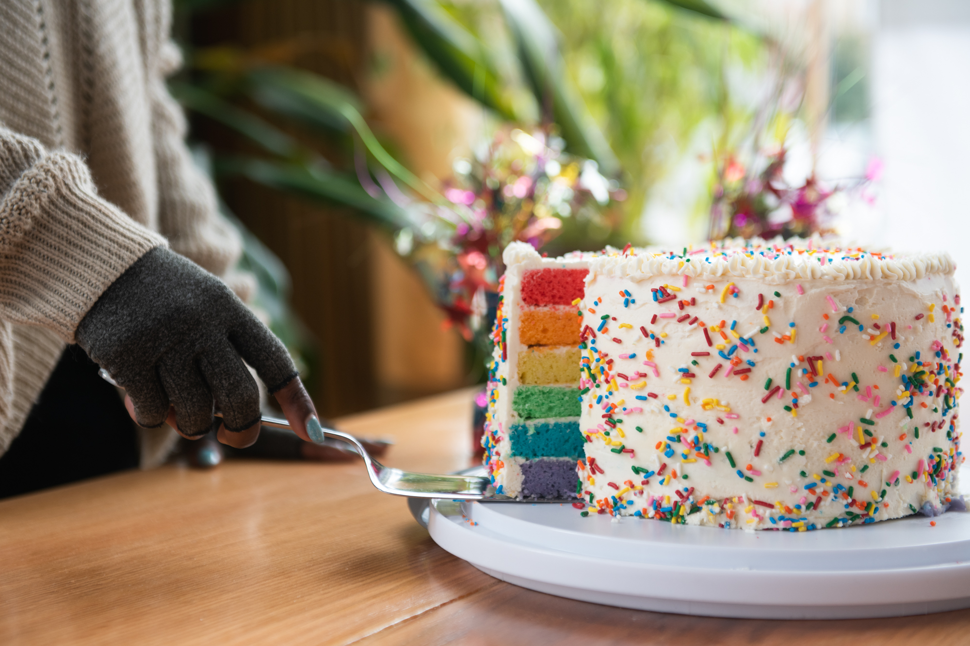 A gloved hand sliced a cake with rainbow layers on the inside and sprinkles on the outside
