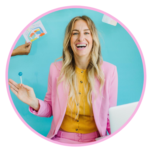 Tiffany is wearing a pink suit with a yellow button down underneath. She's holding a lollipop in one hand and her computer in her other. She's in front of a bright blue background.