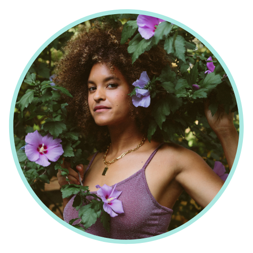 Riley wears a purple spaghetti strap top and stands amidst purple hibiscus blooms and green foliage