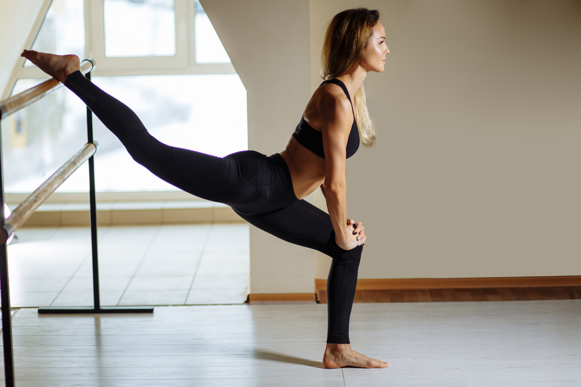 A femme-presenting person in a thin body with long blonde hair stretching one leg behind her in a half split on a barre