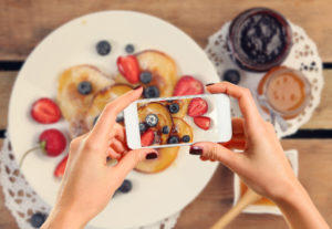 Hands with nails painted maroon photographing a meal on a smart phone