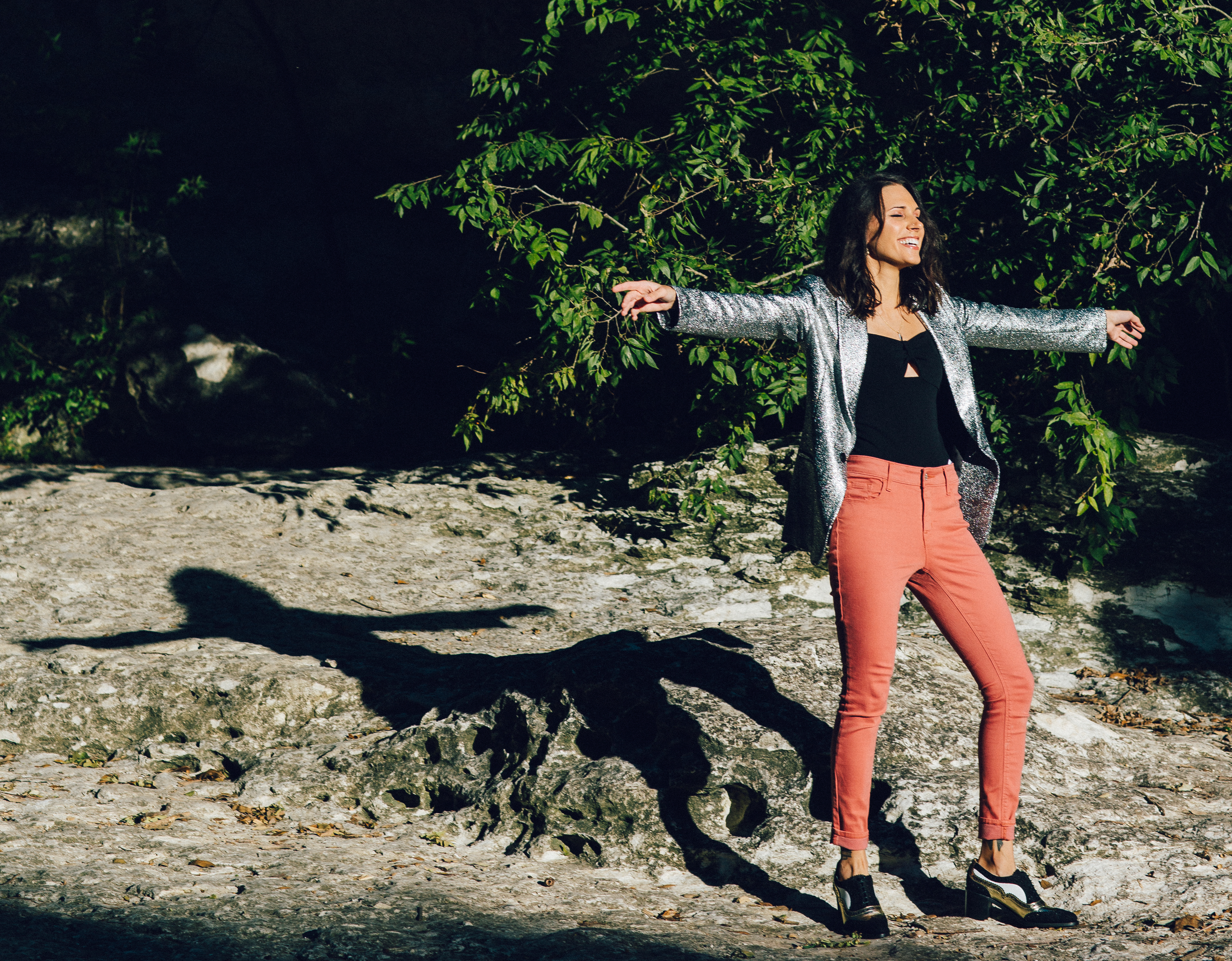 Shohreh stands with arms outstretched in a salmon-colored pants, a black top, and a glittery silver blazer. She is laughing with her face turned toward the sun.
