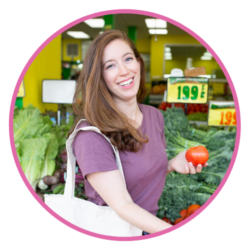 Talia is pictured in the produce section of a grocery store smiling with a reusable bag on one shoulder, holding a tomato in her hand.