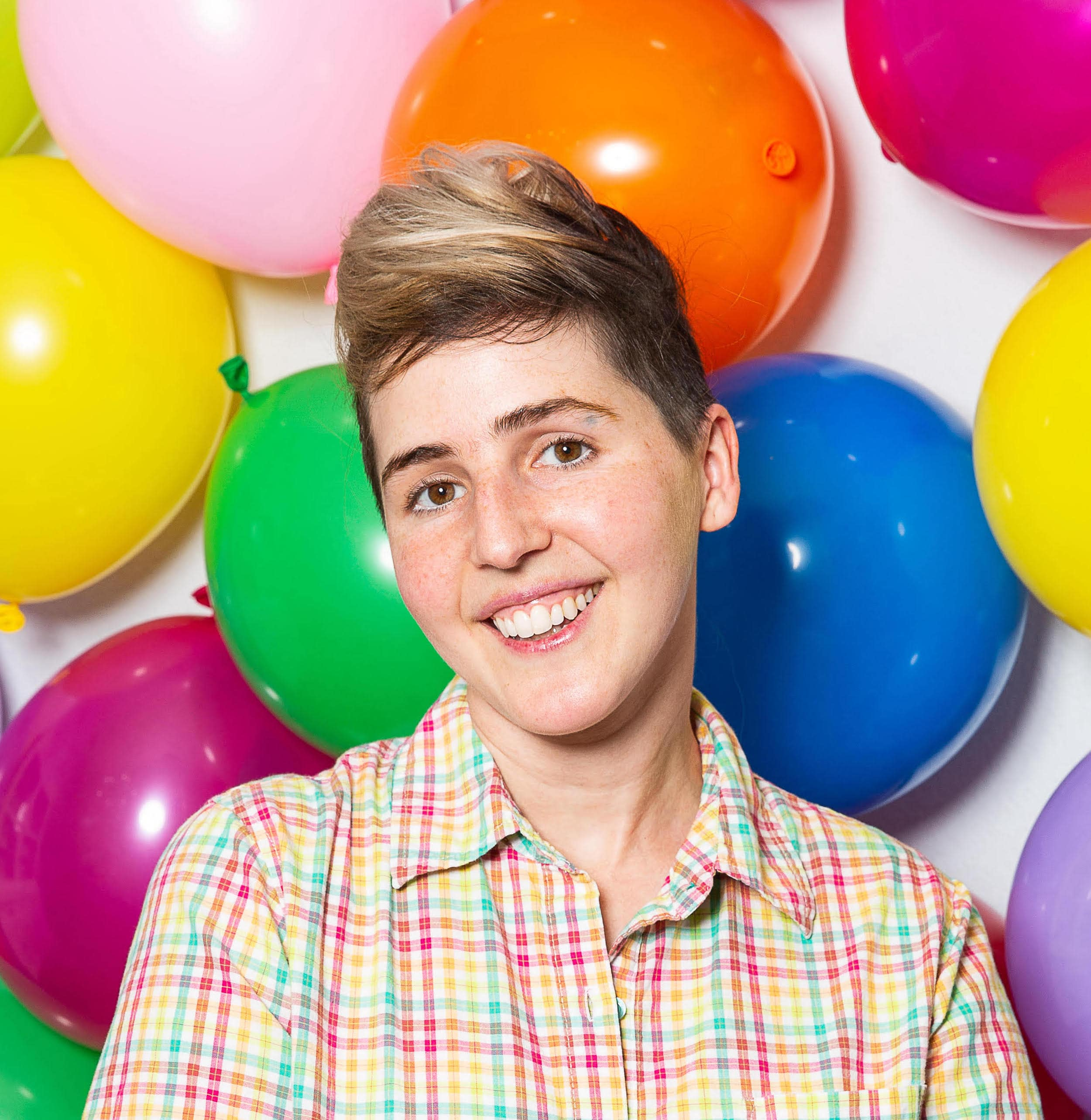 Abi smiles in a brightly colored plaid collared shirt standing in front of a wall of colorful balloons