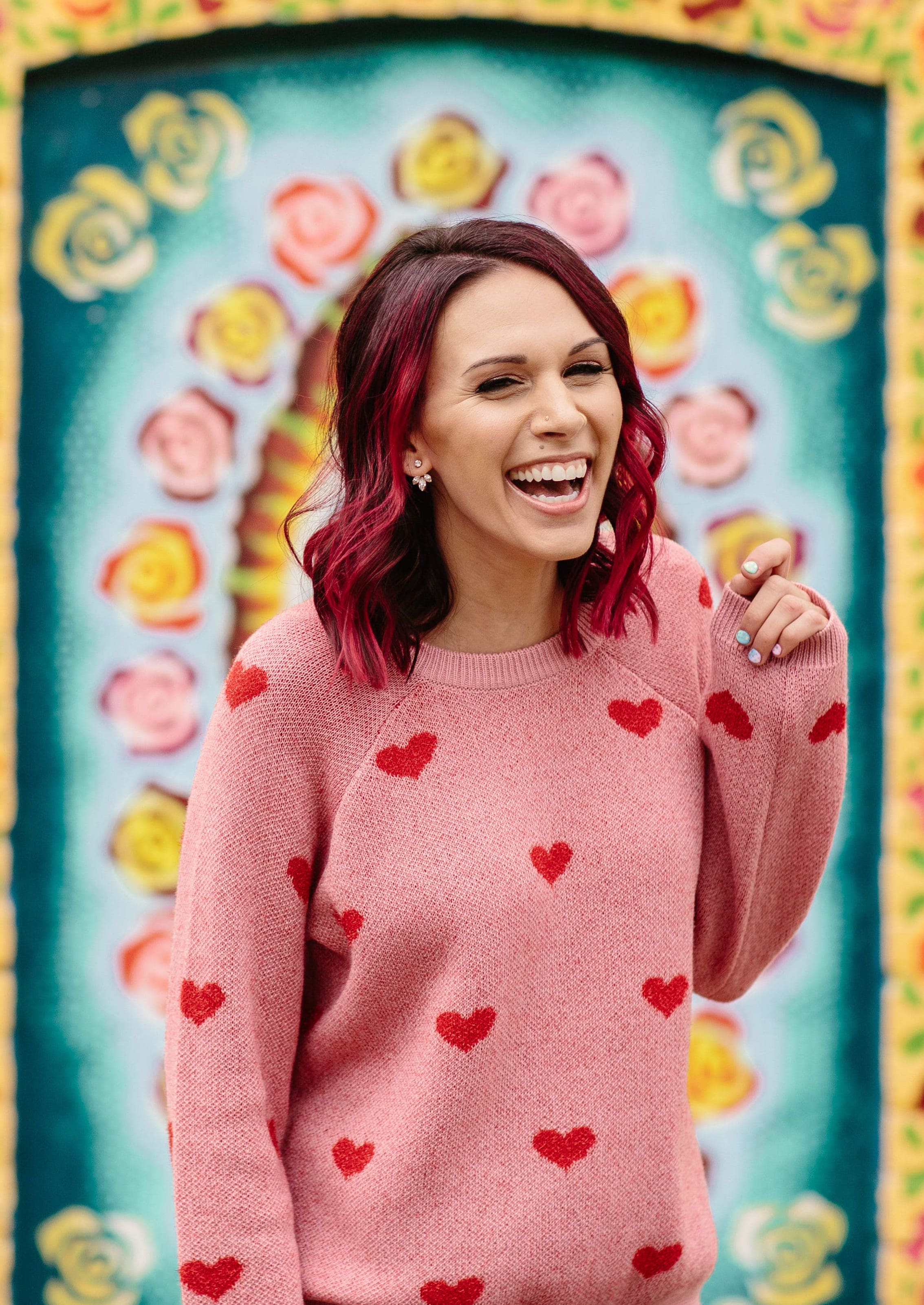 Shohreh has pink hair and wear a pink sweater with red hearts on it. She's laughing while standing in front of a colorful wall that frames her in florals.
