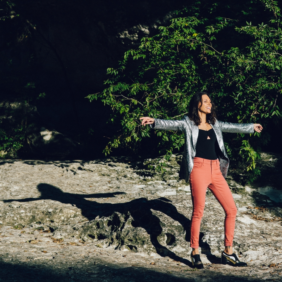 Shohreh stands on a rocky plane outside in salmon-colored pants, a black top, and glittery silver blazer with arms wide open to receive the sunshine